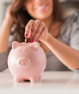 bigstock-Woman-Putting-Coin-In-Piggy-Ba-46096636-254x300